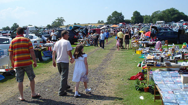A group of people are walking down a path at a car boot sale. The sun is shining and there are lots of stalls with different items on for sale.